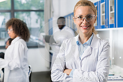 Portrait Of Smiling Woman In White Coat And Protective Eyeglasses In Modern Laboratory, Female Scientist Over Busy