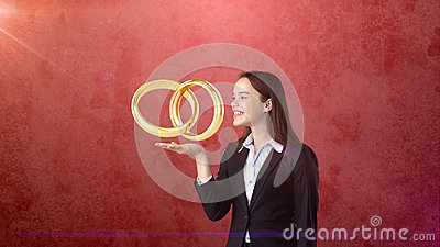 Portrait of young woman holding golden wedding rings on the open hand palm, isolated studio background. Business concept