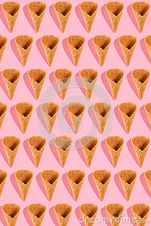 Sugar waffle cone for ice cream arranged in pattern on pink background. The image with copy space can be used as a
