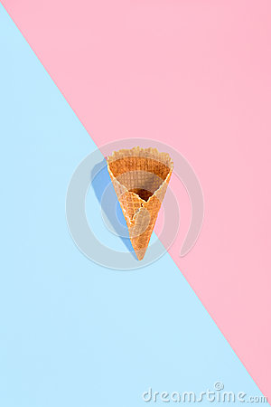 Sugar waffle cone for ice cream arranged in pattern on pink and mint background. The image with copy space can be used