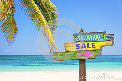 Summer sale written on pastel colored wooden direction signs, beach and palm tree background