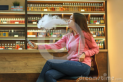 Vape woman. Young cute girl in pink hoodie smoking an electronic cigarette.