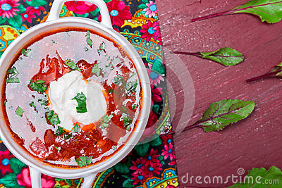 Ukrainian traditional borsch. Russian vegetarian red soup  in white bowl on red wooden background. Top view.  Borscht, borshch wit