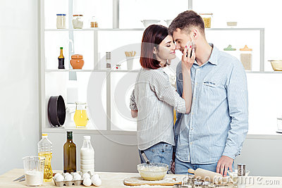 Happy Couple in love cooking dough and kissing in kitchen