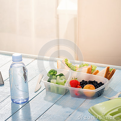 Lunch box with sandwich, vegetables, fruits and bottle of water