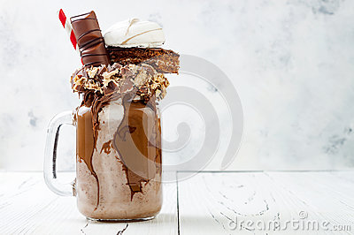 Chocolate indulgent extreme milkshake with brownie cake, marshmallow and sweets. Crazy freakshake food trend.