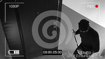 See CCTV as a burglar breaking in through the door with a crowbar
