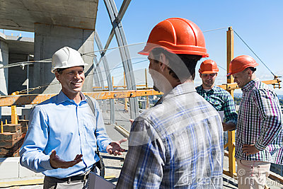 Builders Meeting On Construction Site Architect Talking With Contractor Over Group Of Apprentice