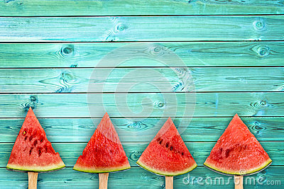 Four watermelon slice popsicles on blue wood background with copy space, summer fruit concept
