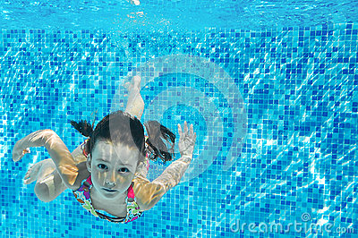 Child swims in pool underwater, happy active girl dives and has fun under water, kid fitness and sport
