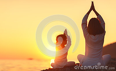 Happy family mother and child doing yoga, meditate in lotus posi