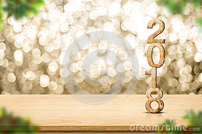 Happy new year 2018 on wood table and blur Christmas tree foreground at blur sparkling gold bokeh light wall,panoramic banner for