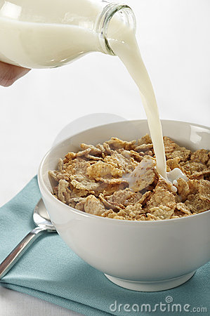 Milk pouring into cereal bowl