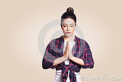 Young brunete woman practising yoga, holding hands in namaste and keeping her eyes closed. Caucasian girl meditating