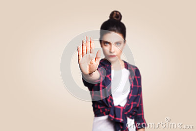 Young annoyed woman with bad attitude making stop gesture with her palm outward, saying no, expressing denial or restriction.
