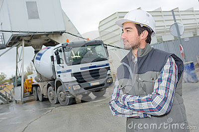 Male engineer standing in front truck on building site