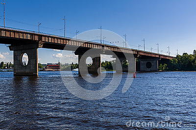Bridge on a river against a blue sky and clouds