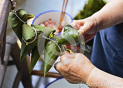Two Hands Tighten the String Over the Leaf to Make Zongzi, Traditional Chinese Rice Dumplings for Dragon Boat Festival