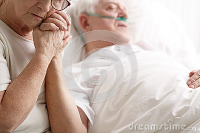 Senior man in hospital bed and his wife holding his hand