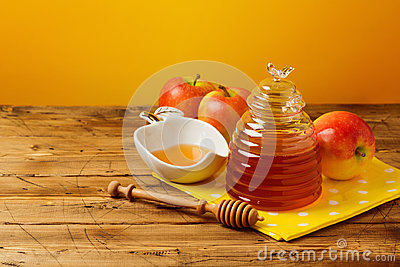 Rosh hashanah jewish new year holiday celebration concept. Honey and apples over yellow background