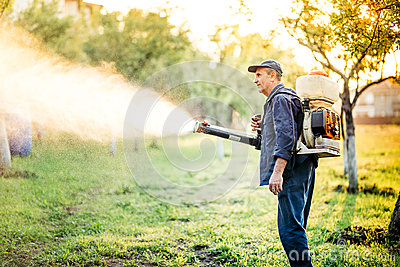 Industrial farm worker doing pest control using insecticide