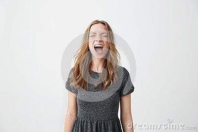 Portrait of emotive young beautiful girl shouting with closed eyes over white background.