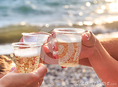 Three friends at the beach are drinking sparkling wine at sunset