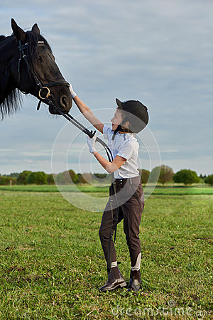 Little girl jockey communicating with her black horse in professional outfit