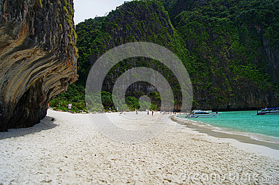 Beautiful white sandy beach beside the blue ocean surrounded by the treed rocks. Thailand.