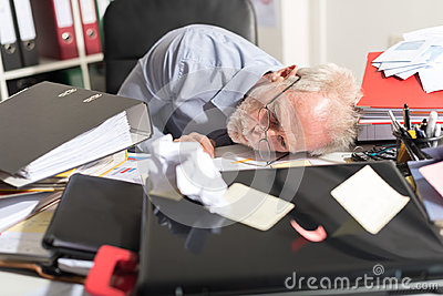 Overworked businessman sleeping on a messy desk