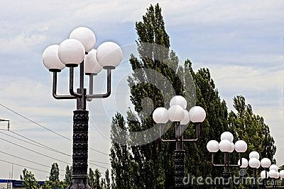 Row with white round shades on street lights in the street