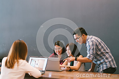 stock image of group of young asian business colleagues in team casual discussion, startup project business meeting or happy teamwork brainstorm