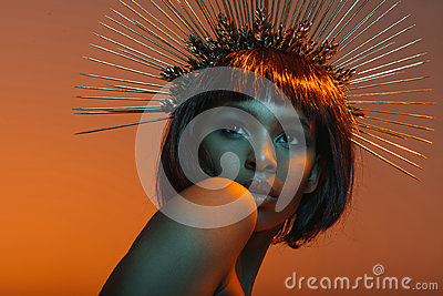African american girl posing in headpiece with needles