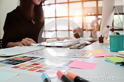 stock image of selective focus on creative table and woman graphic design blur