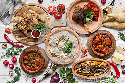 A lot of food on the wooden table. Georgian cuisine. Top view. Flat lay . Khinkali and Georgian dishes