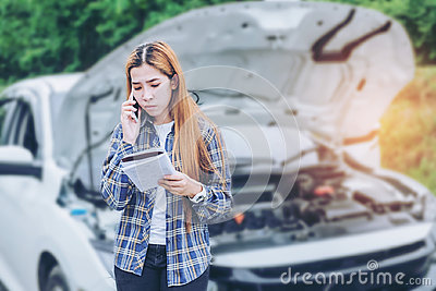 Young Woman calling for assistance with his car broken down by t