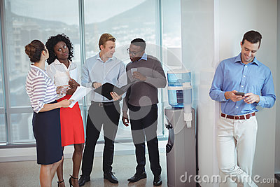 Business colleagues discussing by water cooler
