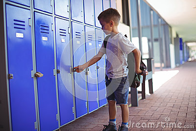 Boy locking locker while wearing bag