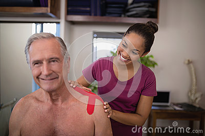 Smiling female therapist applying elastic therapeutic tape on shoulder of shirtless senior male pati