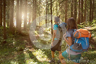 Man and woman with backpack walking on hiking trail path in forest woods during sunny day.Group of friends people summer