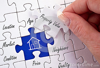 Property Value - female hand with real estate puzzle