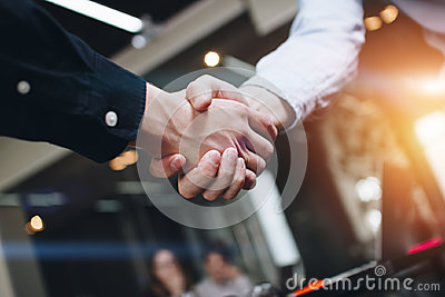 Bussines partners handshakes in modern open space on the background of coworking team on new startup project