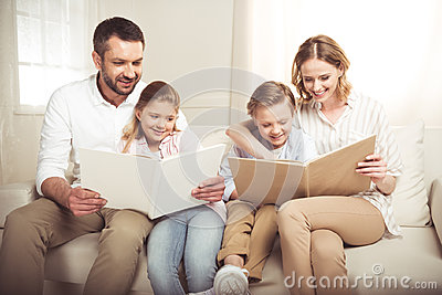 Family with two adorable children sitting together and reading books at home
