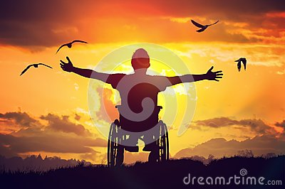 Disabled handicapped man has a hope. He is sitting on wheelchair and stretching hands at sunset
