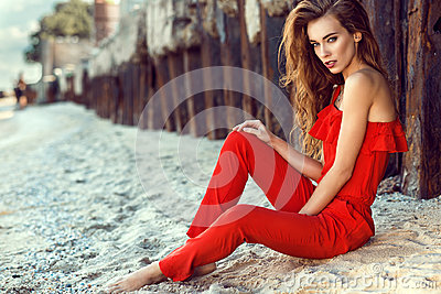 Charming young woman with long hair in coral red one shoulder jumpsuit sitting on the beach at the old rusty piles
