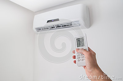 Hand holding remote control for air conditioner on white wall.