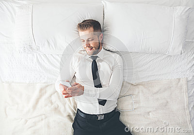 Top view. Handsome businessman lying on bed texting from his smartphone