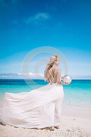 Young blond long hair bride wear a white open back wedding dress and stand on the white sand beach with a pearl. Looking to the se