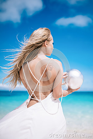 Portrait of the beautiful blond long hair bride in a open back wedding dress stand on the white sand beach with a pearl. Looking t