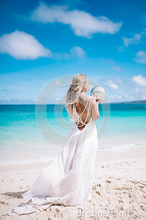 Beautiful blond long hair fiancee in a long white open back wedding dress stand on the white sand beach with a pearl. Looking to